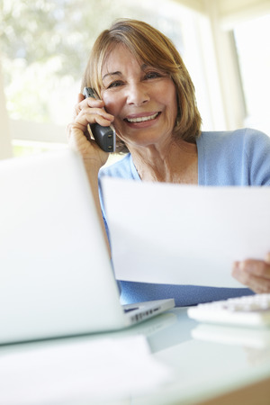 woman with camera: Senior Hispanic Woman Working In Home Office Stock Photo