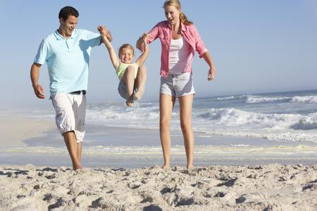 familias felices: Familia que se divierte en la playa