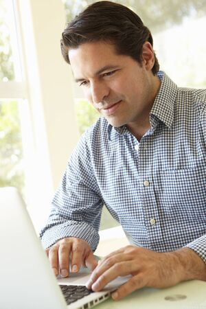 man working computer: Hispanic Man Using Laptop In Home Office