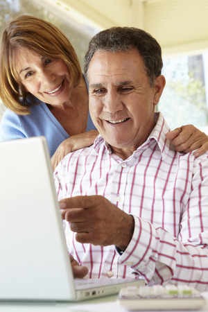 working at home: Senior Hispanic Couple Using Laptop In Home Office