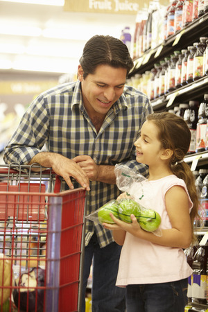 Father and daughter buying fruit in supermarket photo