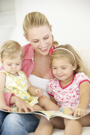 5 10 year old girl: Mother And Daughters Reading Book At Home