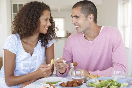 pareja en casa: Pareja joven disfruta de la comida en casa Foto de archivo