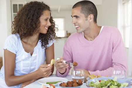 couple home: Young Couple Enjoying Meal At Home Stock Photo