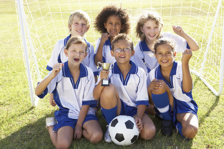 soccer team: Group Of Children In Soccer Team Celebrating With Trophy Stock Photo