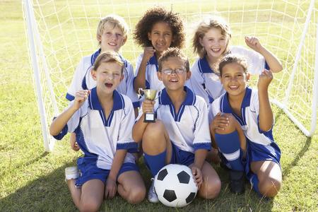 jugando futbol: Grupo de ni�os En Equipo de f�tbol que celebran con el trofeo Foto de archivo