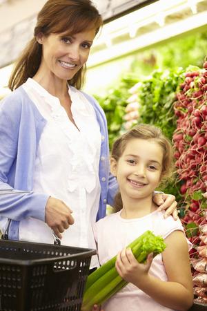 niño empujando: Mother And Daughteer Shopping For Produce In Supermarket Foto de archivo