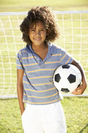 boy: Young Boy With Soccer Ball Standing By Goal Stock Photo