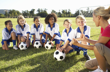 women playing soccer: Group Of Children In Soccer Team Having Training With Female Coach