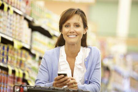 supermercado: Mujer que usa el tel�fono celular en el supermercado Foto de archivo