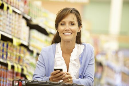 woman shopping cart: Woman using cellphone in supermarket