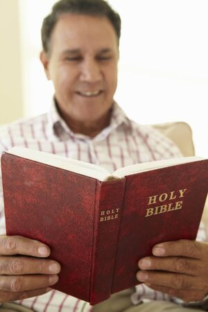 gospels: Senior Hispanic Man Reading Bible Stock Photo
