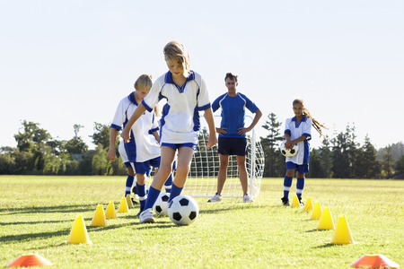 soccer pitch: Group Of Children In Soccer Team Having Training With Coach