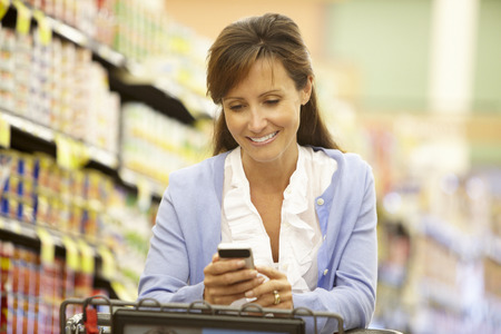 Vrouw met behulp van mobiele telefoon in de supermarkt Stockfoto