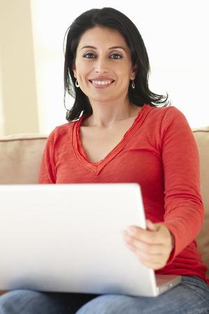 browsing: Hispanic Woman Using Laptop At Home Stock Photo