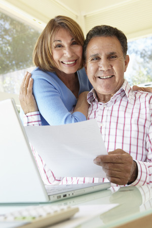 Senior Hispanic Couple Working In Home Office photo