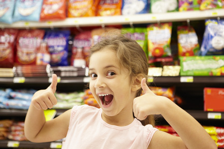 aisle: Girl in confectionery supermarket confectionery aisle
