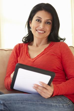 Spaanse Vrouw die tabletcomputer At Home