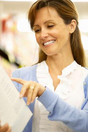 checking ingredients: Woman Reading Ingredients On Packet In Supermarket