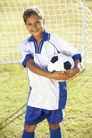 9 year old: Young Girl Dressed In Soccer Kit Standing By Goal
