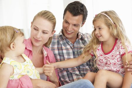 5 10 year old girl: YOung Family Relaxing On Sofa