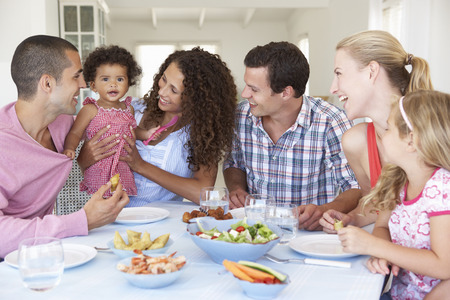 mother cooking: Families Enjoying Meal Together At Home