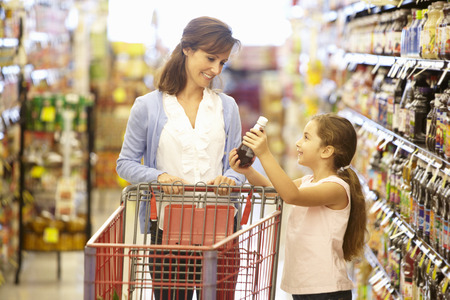 woman shopping cart: Mother and daughter shopping in supermarket