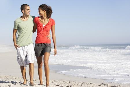Young Couple Walking Along Beach