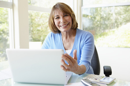 Senior Hispanic Woman Using Laptop In Home Office Stok Fotoğraf