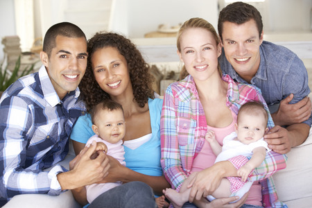 family sofa: Two Young Family With Babies On Sofa At Home