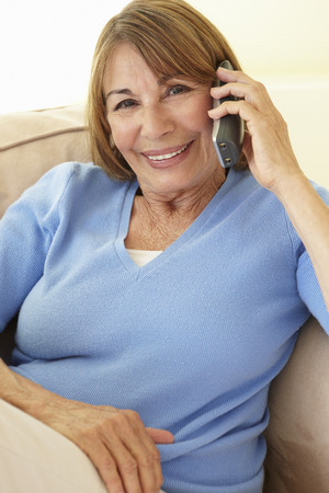 woman on phone: Senior Hispanic Woman Using Cellphone At Home