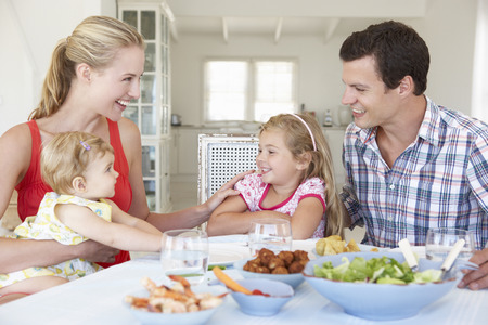 little table: Family Enjoying Meal Together At Home Stock Photo