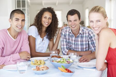 Group Of Young Friends Eating Meal At Home Together photo