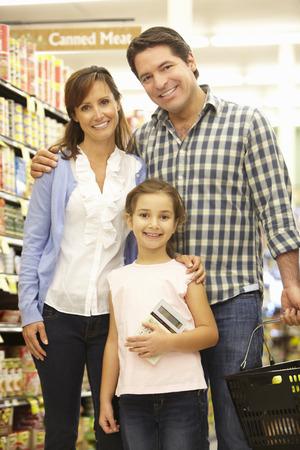 buen vivir: Compras de la familia en supermercado Foto de archivo
