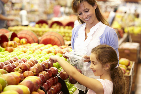 7 year old girl: Mother and daughter buying fruit in supermarket