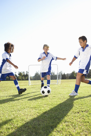 three children: Group Of Boys Playing Football