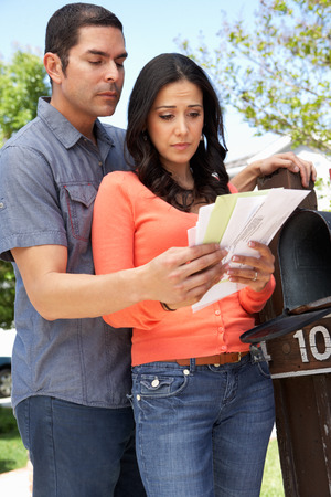 checking: Worried Hispanic Couple Checking Mailbox Stock Photo