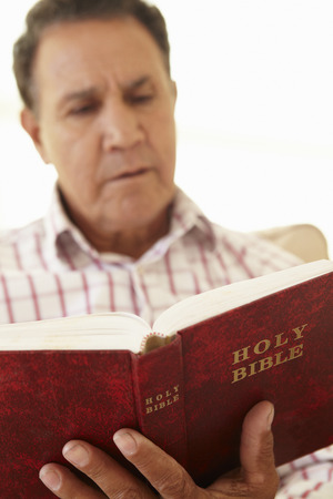 Senior Hispanic Man Reading Bible Stock Photo