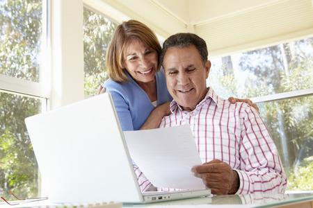 jubilados: Pares hispánicos mayores que trabajan en oficina Inicio Foto de archivo