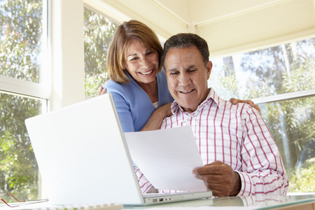 60s adult: Senior Hispanic Couple Working In Home Office