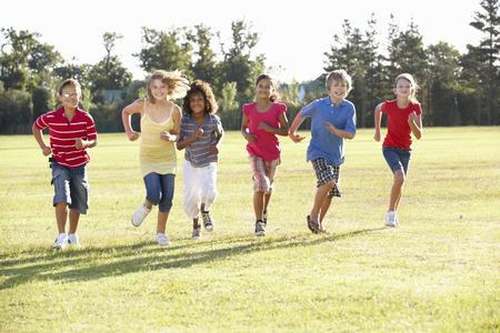 Group Of Children Running Through Countryside Stock Photo