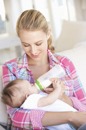 Young Mother With Baby Feeding On Sofa At Home photo