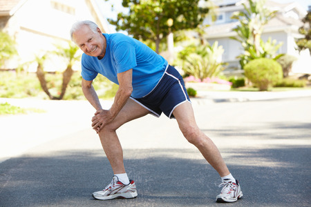 running late: Elderly man warming up for run Stock Photo