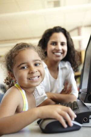 45 years old: Elementary School Pupil With Teacher In Computer Class
