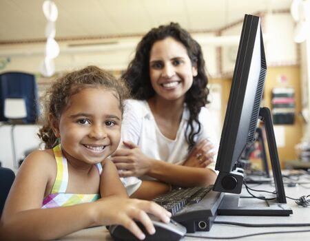 Elementary School Pupil With Teacher In Computer Class photo