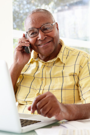 Senior Man On Phone Using Laptop At Home photo