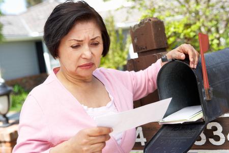 Ongerust Hogere Spaanse Vrouw controleren Mailbox Stockfoto