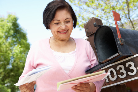 Senior Hispanic Woman Checking Mailbox 免版税图像