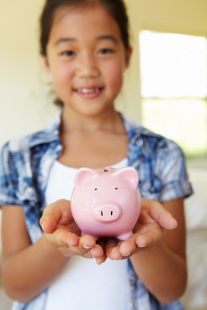 thrifty: Young girl holding piggybank Stock Photo