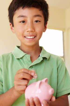 managing money: Young boy putting money in piggybank